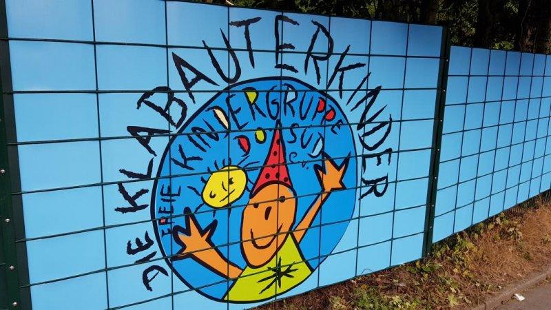 Hellblaue Sichtschutzstreifen mit Kindergartenlogo bedruckt am Zaun befestigt